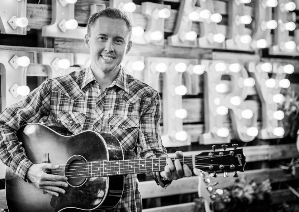 black and white photo of cody carter holding a guitar and wearing a checkered shirt standing in front of lights