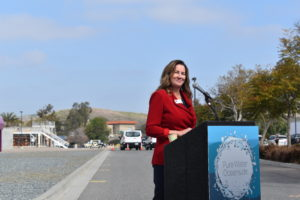 Cari Dale wearing a red jacket standing at a podium