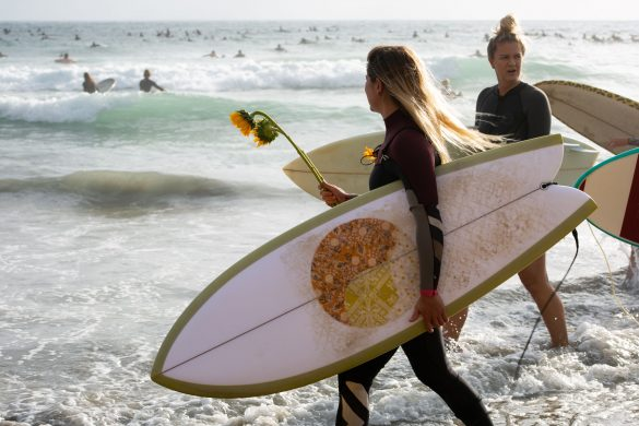 Protesters carry flowers and surfboards during a paddle out event on June at Moonlight Beach. Photo by Caitlin Steinberg