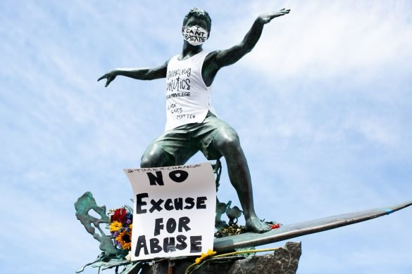 "A sculpture of a surfer, known locally as the ""Cardiff Kook,"" was adorned with a face mask featuring the words, ""I Can't Breathe,"" and a sign reading, ""No Excuse For Abuse."" Photo by Caitlin Steinberg"